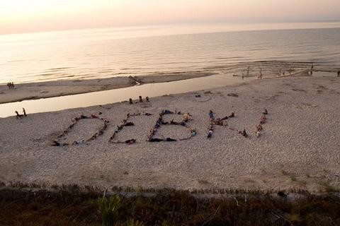 Nie było łatwo, dopiero za 4 podejściem się udało. 80 osób na plaży w Dębkach tworzy wspólny napis. (2009 r.)